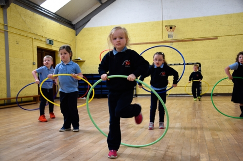Junior Infants using hoops to learn to skip